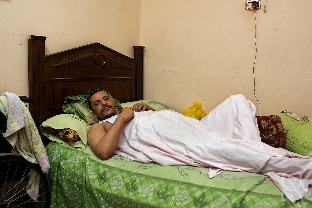 Ashraf Mohammed al-Shahat, age 40, lies partially paralyzed in bed at his home in the Matareya district of Cairo, Egypt July 27,2011. Al-Shahat, a deaf mute, was shot multiple times by Egyptian police during the revolution in Jan 2011 while trying to save his nephew. (Photo by Scott Nelson for Stern)
