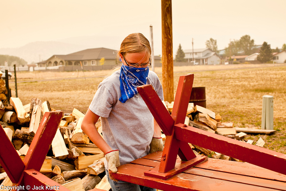 "04 JUNE 2011 - EAGAR, AZ: Kelli Elliott (CQ) wore a bandana because of smoke from the Wallow Fire while she cleaned up the land around Life in Christ Fellowship Church in Eagar Saturday. The fire grew to more than 140,000 acres early Saturday with zero containment. A ""Type I"" incident command team has taken command of the fire.    PHOTO BY JACK KURTZ"