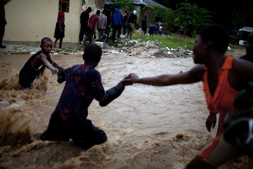 After hurricane Tomas went through Haiti, the city of Leogane has been totally flooded by the heavy rain and the overflow of the river Roullorne.///A young Haitian (L) tries to go out of the the muddy water with the help of his friends, in a street of Leogane during hurricane Tomas.
