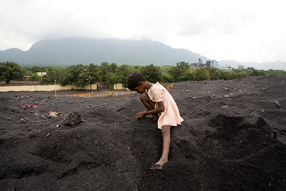 Villagers sift through waste from chromite-ore mines in search of scraps to sell back to merchants. Many bring their to help them. Sukinda, Orissa, India