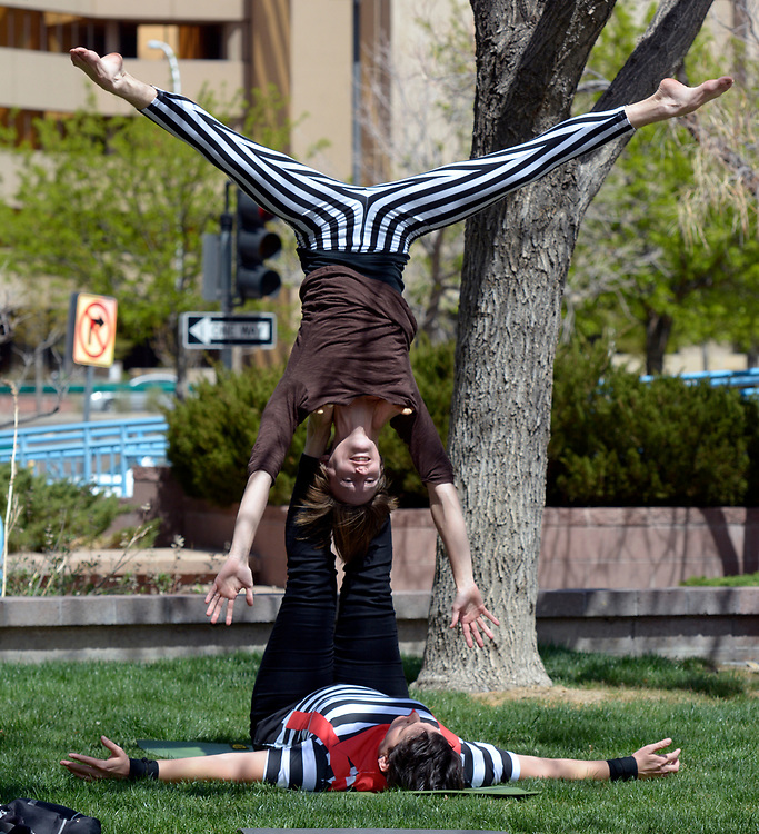 """gbs040217r/ASEC -- Alex Ross-Raymond, top, and Dee Reed,  both of Albuquerque, warm up before performing during the Rally Against Sexual Violence in the Albuquerque Civic Plaza on Sunday, April 2, 2017. They practice """"acroyoga"""" as a way to teach sexual violence prevention. (Greg Sorber/Albuquerque Journal)"""