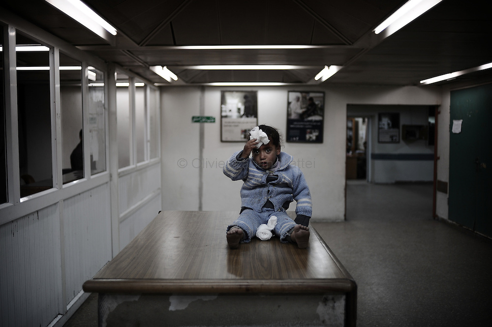 A wounded Palestinian girl holds a wad of cotton wool against her forehead as she sits on a desk at Al-Shifa hospital in Gaza City on January 21, 2009. Over 1,330 Palestinians were killed and at least 5,450 wounded during Israel's 22-day offensive in the Gaza Strip. Some 65 percent of the dead were civilians, including 400 children and 100 women.