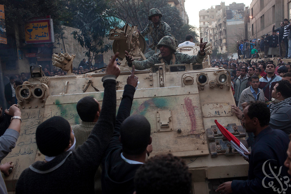 Protesters plead with an Egyptian Military armored personnel carrier crew to use their weapons against nearby riot police firing on them during a street battle near the interior ministry in downtown Cairo January 29, 2011. Although refusing to use their weapons against the police, the Egyptian soldiers in the carriers appeared sympathetic to the protesters, moving the vehicles into positions to provide cover from the police who were firing buck shot shells and tear gas at the large crowd.