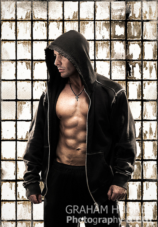 Muscular male in hoodie with top off in front of glass wall