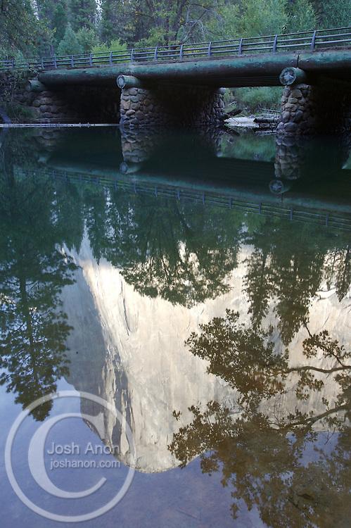 El Capitain reflects into the Merced river near a bridge in Yosemite National Park, California.