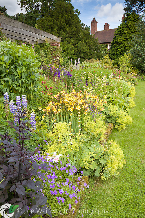 A richly planted herbaceous border next to the Pergola Walk at Abbeywood Gardens, Cheshire.