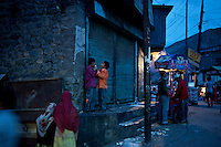 Friends share an ice cream cone in the bazaar in Kargil, India