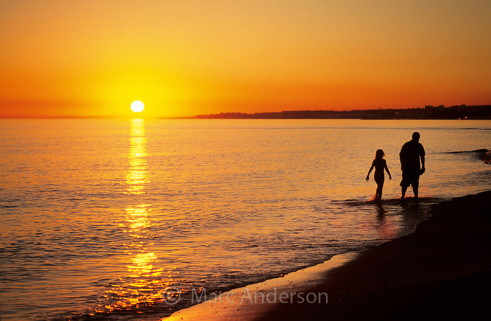 Silhouette of a boy & girl walking on a Mediterranean beach at sunset, Costa Del Sol, Spain