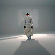 Terence Koh, Canadian conceptual artist, known for his queer, punk, and pornographic sensibilities, has a new installation at the Whitney Museum of American Art in New York City. Here he prepares for his installation by dressing in a traditional Japanese kimono before entering an all white space with a powerful spotlight.
