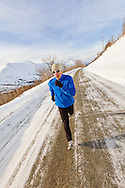 A male jogger jogging along Hiland Road in South Eagle River with the Chugach Mountains and Chugach State Park in the background in Southcentral Alaska. Winter. Afternoon. MR.