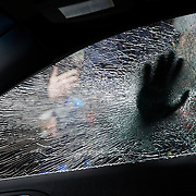 WASHINGTON, USA - January 20: An anti-Trump protestor tries to push his hand through the window of a limousine during clashes with police after President Trump was sworn into office in Washington, USA on January 20, 2017.