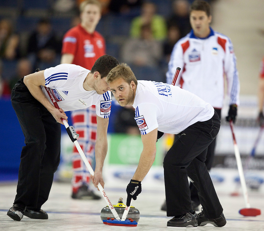 France's third Tony Angiboust looks up while sweeping skip Thomas Dufour's stone during France's tie breaker against Norway at the Ford World Men's Curling Championships in Regina, Saskatchewan, April 8, 2011.<br /> AFP PHOTO/Geoff Robins