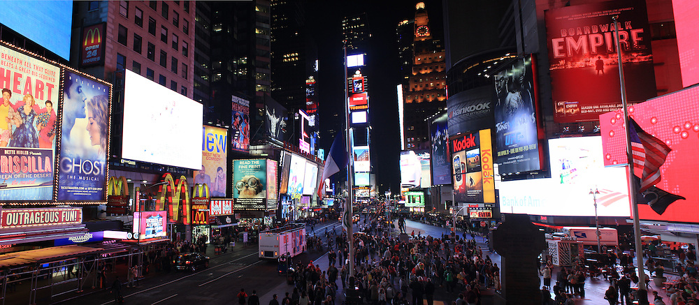 A panoramic view of Time Square, New York at night time. Times Square is the major commercial intersection in Midtown Manhattan, New York City, at the junction of Broadway and Seventh Avenue and stretching from West 42nd to West 47th Streets. Time Square, New York, USA. 27th April 2012. Photo Tim Clayton.Note to Editors. This image is a composite of two images taken a split second apart and merged in editing.