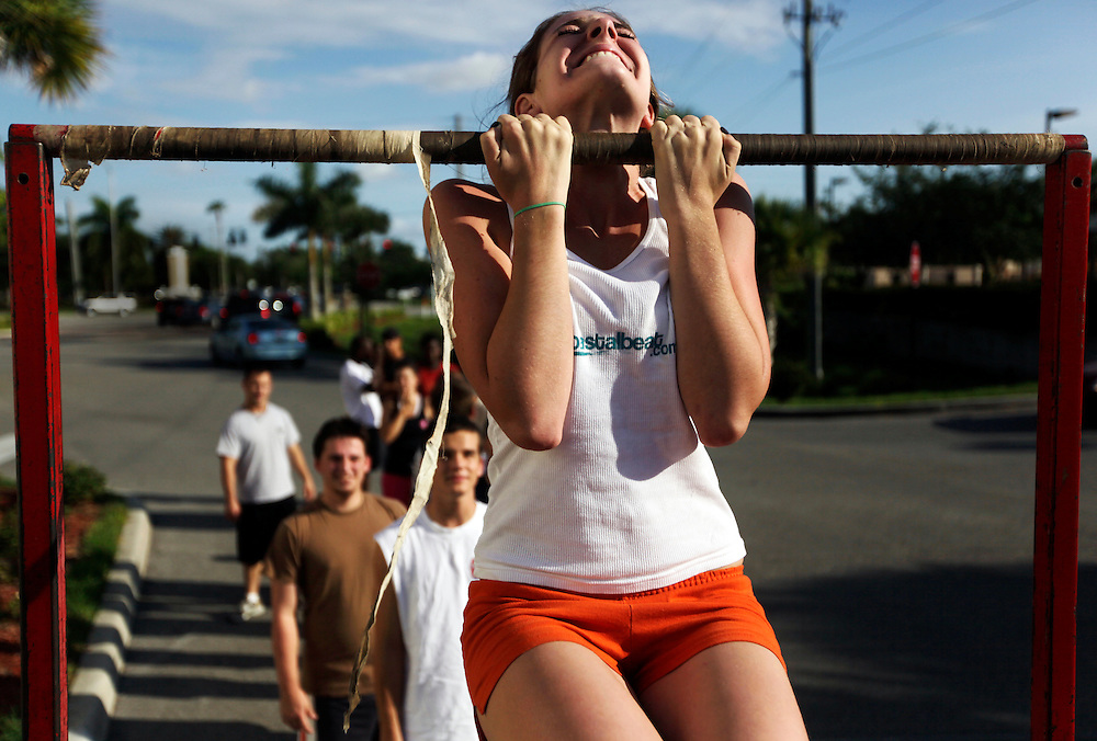 """Elaine Neal strains to keep her chin above the bar in a flexed arm hang during a Marine Corps Initial Strength Test at the recruiting sub-station off Pine Ridge Road in Naples on June 3, 2009. The minimum for a female Marine in the flexed arm hang is 15 seconds, but Neal finished with a personal best of 70 seconds. Neal said that for a lot of activities she generally loses interest after time and ends up quitting, but the choice to be in the Marines is different. """"That's another reason why I really like [the Marines], because I'm trying my best on something,"""" Neal said. Greg Kahn/Staff"""