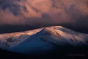 Last blast of evening sunlight over a stormy winter mountainscape in the Carneddau range, Snowdonia, Wales.  Spindrift blows off the ridge between Carnedd Dafydd and Carnedd Llewelyn.