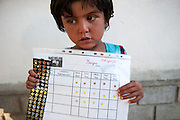 5 year old Omeda (MDR TB) holds up her star chart. She gets a sticker every time she takes her medicine properly. Treating young children with TB can be very complicated and incentives like the sticker stars are used to help them take the drugs they need during their treatment.