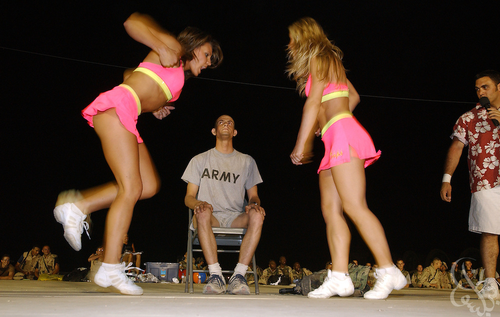 Cheerleaders for the American football team the Baltimore Ravens dance around U.S. Army Sgt. Steven Jacob Waldon during a performance at the coalition forces'' Kandahar airfield May 08, 2002 in southern Afghanistan. The cheerleaders are visiting the airbase as part of a USO Tour for coalition forces deployed across the Middle East and Central Asia for Operation Enduring Freedom..