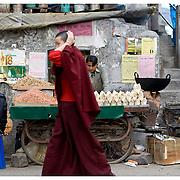 Buddhist monk passing market stall. Macleod Gang, Himashal Pradesh, India.