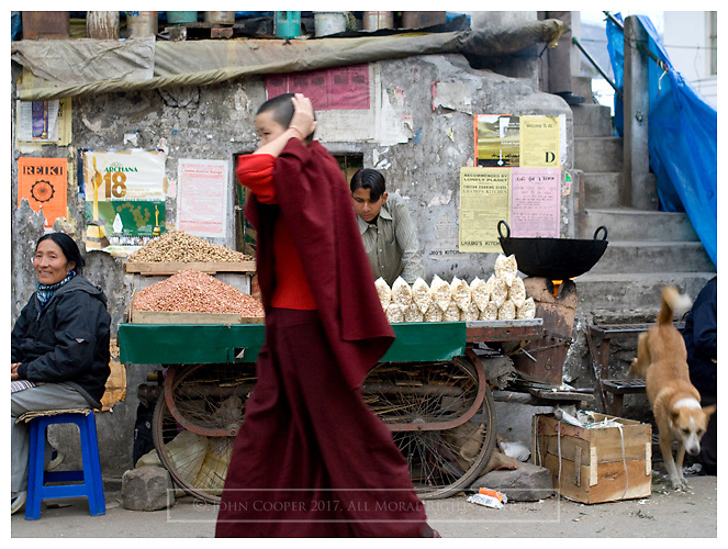 Buddhist monk passing market stall. Macleod Gang, Himashal Pradesh, India.