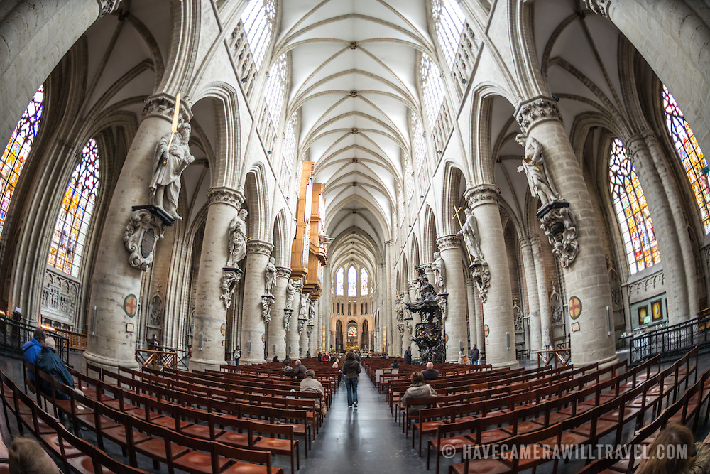 A wide-angle shot of the nave at the Cathedral of St. Michael and St. Gudula (in French, Co-Cathédrale collégiale des Ss-Michel et Gudule) looking from the entrance down towards the altar. A church was founded on this site in the 11th century but the current building dates to the 13th to 15th centuries. The Roman Catholic cathedral is the venue for many state functions such as coronations, royal weddings, and state funerals. It has two patron saints, St Michael and St Gudula, both of whom are also the patron saints of Brussels.