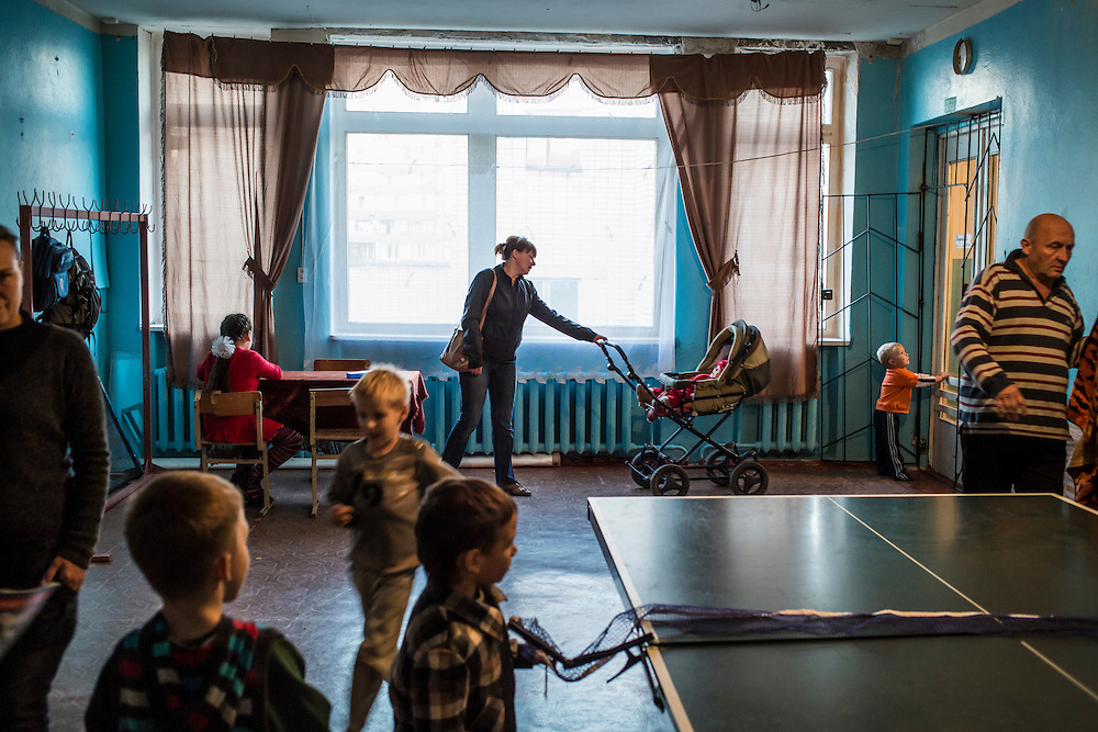 DNIPRODZERZHINSK, UKRAINE - OCTOBER 11: Children and adults in a corridor at the sports school where about 60 people displaced by fighting in Eastern Ukraine live on October 11, 2014 in Dniprodzerzhinsk, Ukraine. The United Nations has registered more than 360,000 people who have been forced to leave their homes due to fighting in the East, though the true number is believed to be much higher.(Photo by Brendan Hoffman/Getty Images) *** Local Caption *** ***