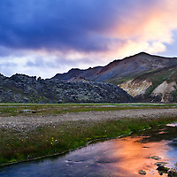 Colorful clouds reflecting in a small creek near the camping in the geothermal area of Landmannalaugar in the Iceland Highlands