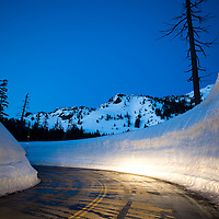 Headlights and taillights reflecting off a snow wall at dusk on the road to Crater Lake near Rim Village, Oregon