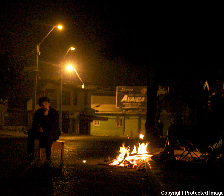 Man stays warm in Constiución by staying near a bonfire despite the issued curfew imposed because of the looting after the earthquake