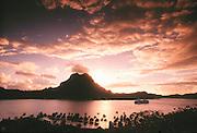 Sunrise over Mt. Pahia and Vaitape village, Bora Bora Lagoon resort in foreground, MV Paul Gaugin cruise ship in lagoon; Bora Bora, Tahiti.