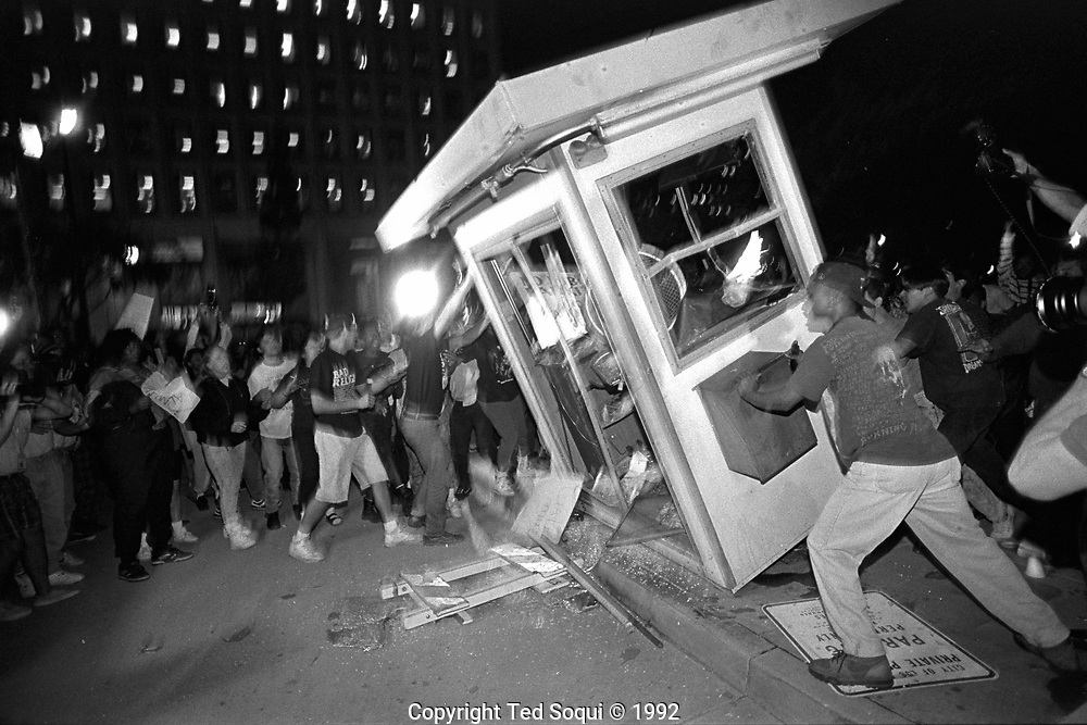Rioters overturn and burn a parking kiosk near Parker Center, LAPD headquarters, in downtown Los Angeles. 4/29/1992<br /> <br /> 25 before and after LA92 photo project.