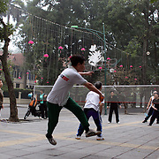 An group of elderly residents play a game a badminton at day break on the streets of Hanoi, Vietnam.. For a county not know for it's sporting prowess, Hanoi, Vietnam's capital, appears to be gripped in a fitness frenzy. Before 6am street corners, parks and lake sides are a hive of activity as keep fit classes, Tai chi and personal exercise regimes are seen in abundance around the city. Particularly noticeable are Women's keep fit classes, often accompanied by loud poor quality western disco beat music as the occupants of the city get fit come rain or shine. Hanoi, Vietnam. 18th March 2012. Photo Tim Clayton