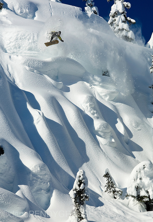 Legendary Pro Snowboarder Shin Campos airs into a steep fluted face in the Coast Mountain backcountry near Whistler, BC, Canada.