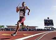 Gordon Butler of Edmond Santa Fe High School in Oklahoma runs his leg of the 4x400-meter relay as the following heats' teams watch in the background.