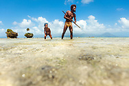 Traditionally dressed Ni Vanuatu father showing his son how to shoot fish with a bow and arrow. The men of Rah Lava have fished with a bow and arrow in the crystal clear waters around the island for countless generations.  Rah Lava Island, Torba Province, Vanuatu
