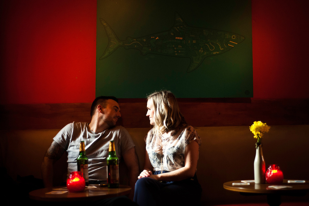 Manchester, UK - 4  August 2012: a couple sits drinking beer at The Temple bar in Manchester below a shark painting