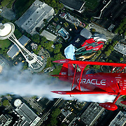 """The Oracle Challenger, a unique 400 horespower stunt plane, makes a pass over a familiar Seattle landmark while on an aireal tour of the area on Thursday August 5, 2004 in preparation for  the KeyBank Airshow at SEAFAIR.  Sean Tucker, pilot of the plane, was recently named by the Smithsonian Air and Space Museum as one of the twenty-five """"Living Legends of Flight.""""   The highly regarded pilot has won numerous awards for airshow showmanship and aerobatics at competitions and airshows across the nation.  Joshua Trujillo / Seattle Post-Intelligencer"""