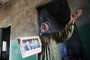 The mother of 24 years old student Abdullah Abdul-Qader stands with his portrait inside her grime coated house. Her son was killed during the lastest attack by syrian army. The village of Bashirija was beeing attacked by syrian Army in early April, leaving serveral people dead. Many houses were set on fire and livestock were shot dead by Assad loyal forces raging for two days. Later nighbours buried bodies of inhabitants hasty in a mass grave.