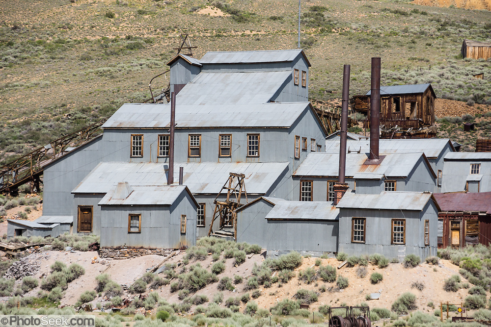 """The gray-metal-sided Standard Stamp Mill is preserved at Bodie, California's official state gold rush ghost town. Bodie State Historic Park lies in the Bodie Hills east of the Sierra Nevada mountain range in Mono County, near Bridgeport, California, USA. After W. S. Bodey's original gold discovery in 1859, profitable gold ore discoveries in 1876 and 1878 transformed """"Bodie"""" from an isolated mining camp to a Wild West boomtown. In the 1870s, the Bunker Hill Mine, later renamed the Standard Mining Company, made a rich strike of gold and silver ore yielding nearly $15 million in 25 years. By 1879, Bodie had a population of 5000-7000 people with 2000 buildings. At its peak, 65 saloons lined Main Street, which was a mile long. Bodie declined rapidly 1912-1917 and the last mine closed in 1942. Bodie became a National Historic Landmark in 1961 and Bodie State Historic Park in 1962."""