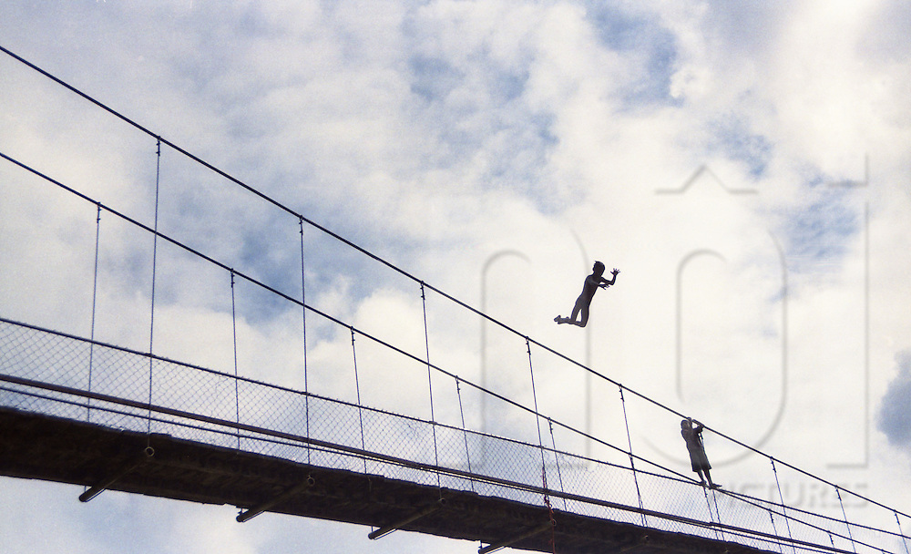 Two young Cambodian boys jump from a bridge into the river below, Cambodia, Southeast Asia