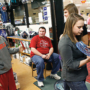 Karissa Shiflet, 16, left, jokes around with Megan Weir, 16, and pro shop employee Evan Nash as pro shop manager Alan Cooke, right, gets Blair Westerman, 16, sized for her ball. Every player on the team is provided with a custom-fitted ball for the duration of their high school career. Varsity players and the first J.V. team all have three or four balls.