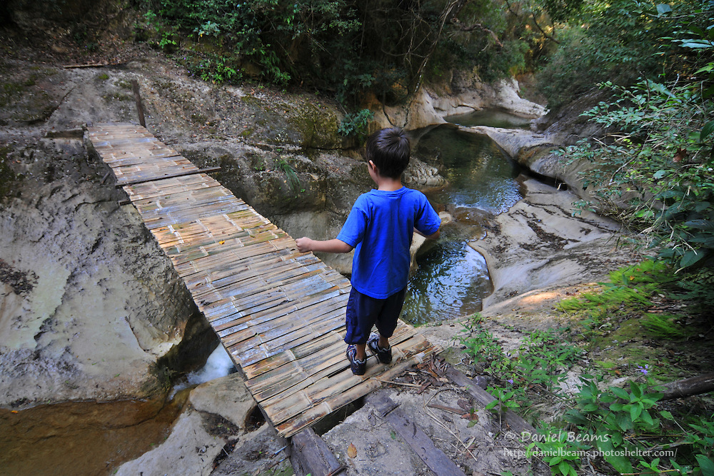 Boy walking across a narrow foot bridge in Santa Cruz, Bolivia