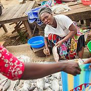 LÉGENDE: Une vendeuse de poissons s'apprête à découper et emballer du poisson pour une cliente. LIEU: Marché de Chagoua, N'Djaména, Tchad. PERSONNE(S): Une vendeuse de poissons assis tenant dans sa main gauche un poisson et à sa main droite un couteau. (Premier plan) la main d'une femme tentant un sac à plastique.