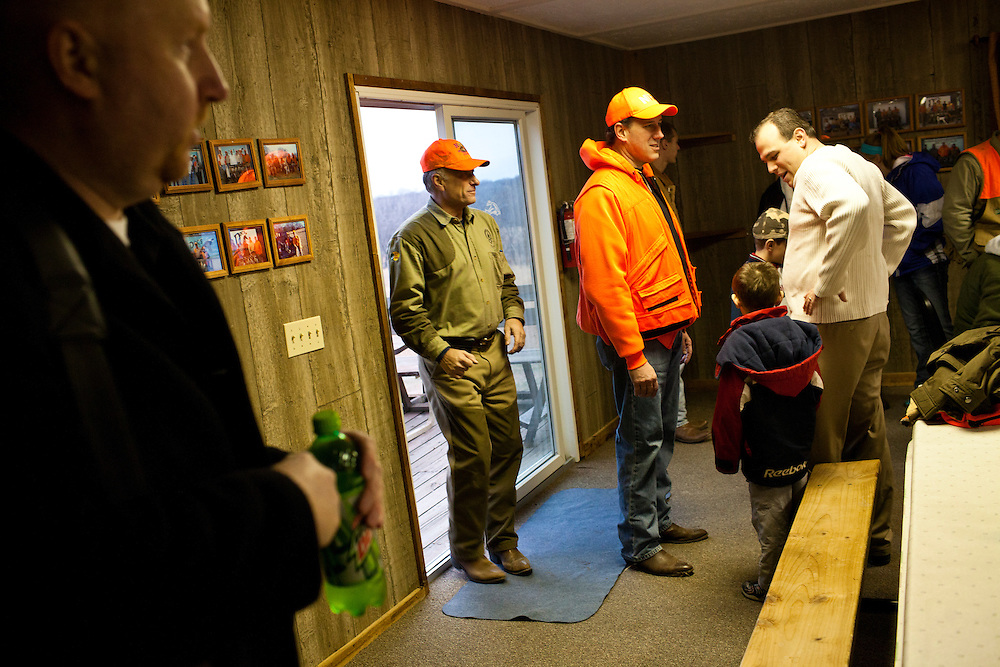Republican presidential candidate Rick Santorum, third from left, talks with hunters after participating in a pheasant hunt on Monday, December 26, 2011 in Adel, IA.