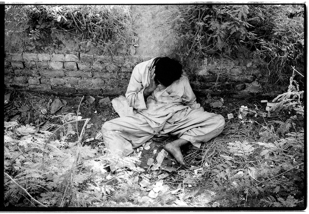 A heroin addict lies comatose in the drainage ditch alongside the main Peshawar - Islamabad road following a probable overdose. ..Record opium crops in neighbouring Afghanistan have resulted in a cheap, affordable and plentiful supply of heroin and opium in Pakistan...In the frontier town of Peshawar, a gram of heroin sells for 100 rupees, little more than a dollar. Most addicts smoke or 'chase the dragon', some inject but the inaccessibility of syringes dictate most addicts smoke the drug...Opium can be found in its pure form, fresh from record harvests in Afghanistan. Most is processed into heroin in the many factories along the Afghan / Pakistan borer, but some is retained, especially in the tribal province, for 'traditional medicinal' purposes such as bile din tea for curing arthritis and flu symptoms...Along the Peshawar – Islamabad road addicts prepare heroin for smoking and injecting in full view of passers by on one of the countries busiest roads..
