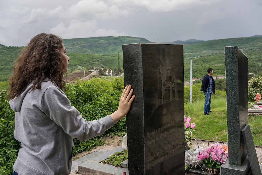 A woman mourns a fighter killed in the 1990s war between Armenia and Azerbaijan following a ceremony commemorating both the victory over Nazi Germany in the Second World War as well as the fall of the strategic town of Shushi to Armenian forces on Monday, May 9, 2016 in Stepanakert, Nagorno-Karabakh.