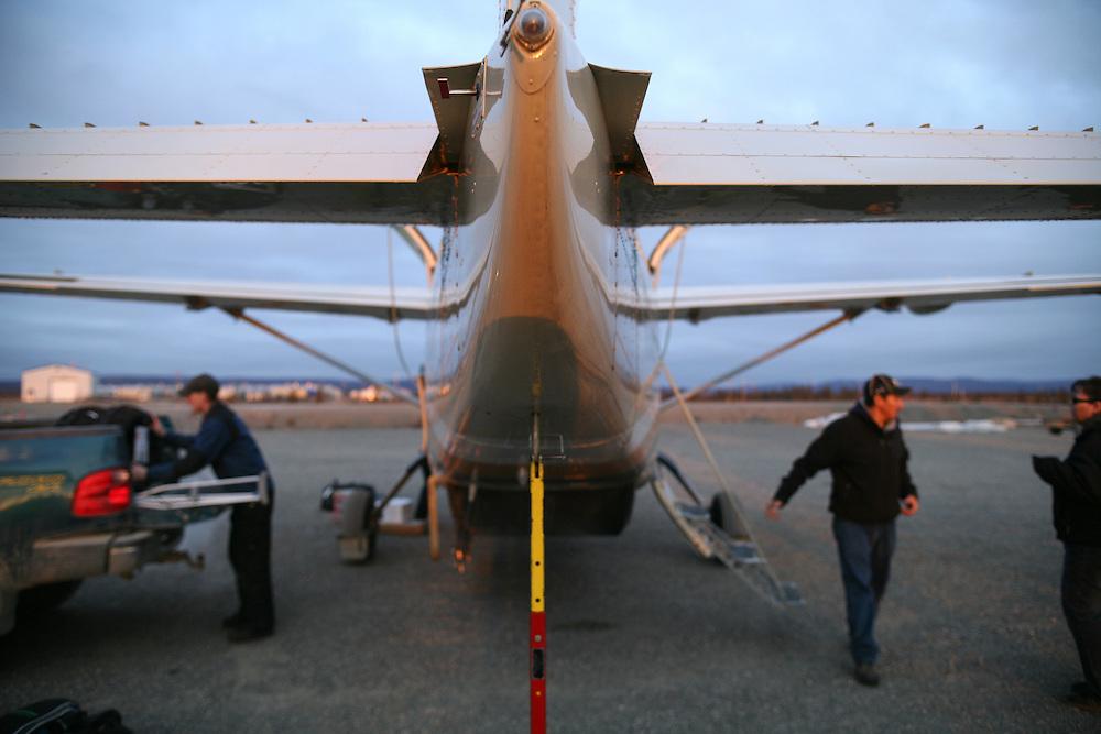 Men unloading the plane that supplies the stores in Noatak, Alaska. 2009