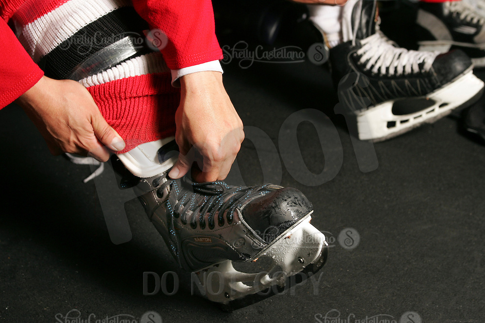 2005:  Man laces up his Easton ice skates before a hockey game.