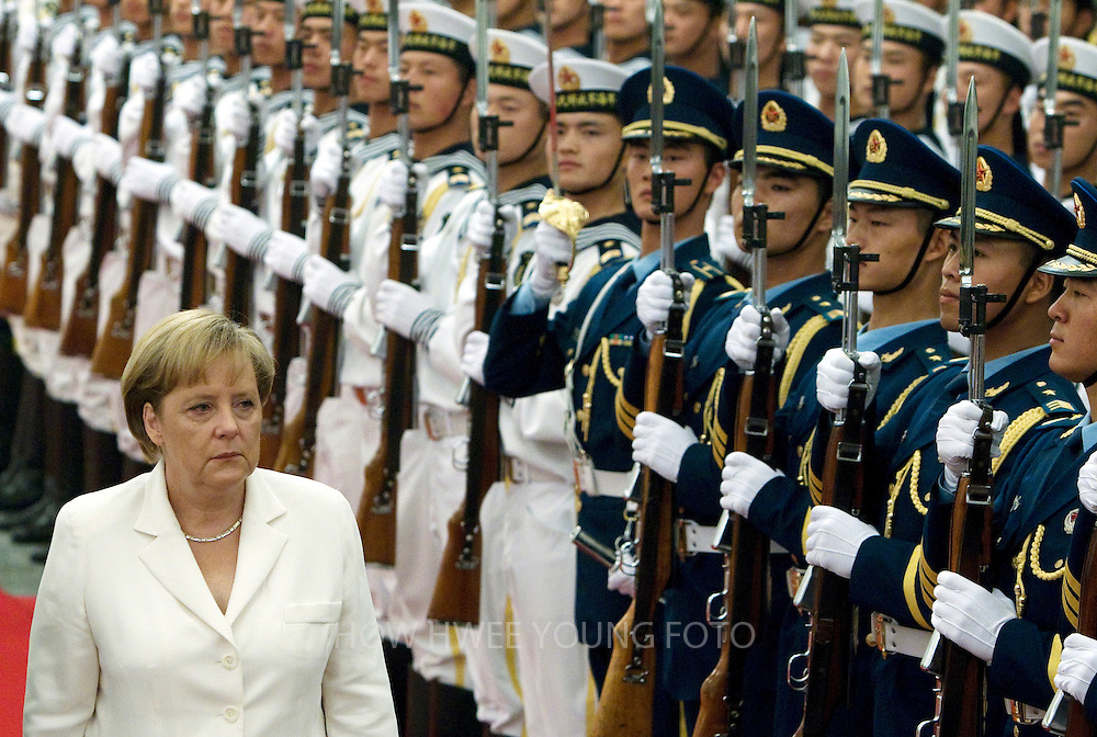 epa02249854 German Chancellor Angela Merkel (L) and Chinese Premier Wen Jiabao (unseen) review the guard of honours at a welcome ceremony in the Great Hall of the People in Beijing, China on 16 July 2010. The German Chancellor is in China for an official visit from 15-18 July 2010.  EPA/HOW HWEE YOUNG