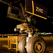 """The giant nosewheel of a Boeing 747-400 airliner is parked on the apron area during its overnight turnround at Heathrow Airport. The engineering of this magnificent piece of aviation design is highlighted by the headlights of an airfield vehicle and the tyres sit firmly on the tarmac at an exact parking spot according to the aircraft's length in order for it to be met by air bridges and service trucks. The nose wheel is used for steering the jet when on the ground. From writer Alain de Botton's book project """"A Week at the Airport: A Heathrow Diary"""" (2009). ."""