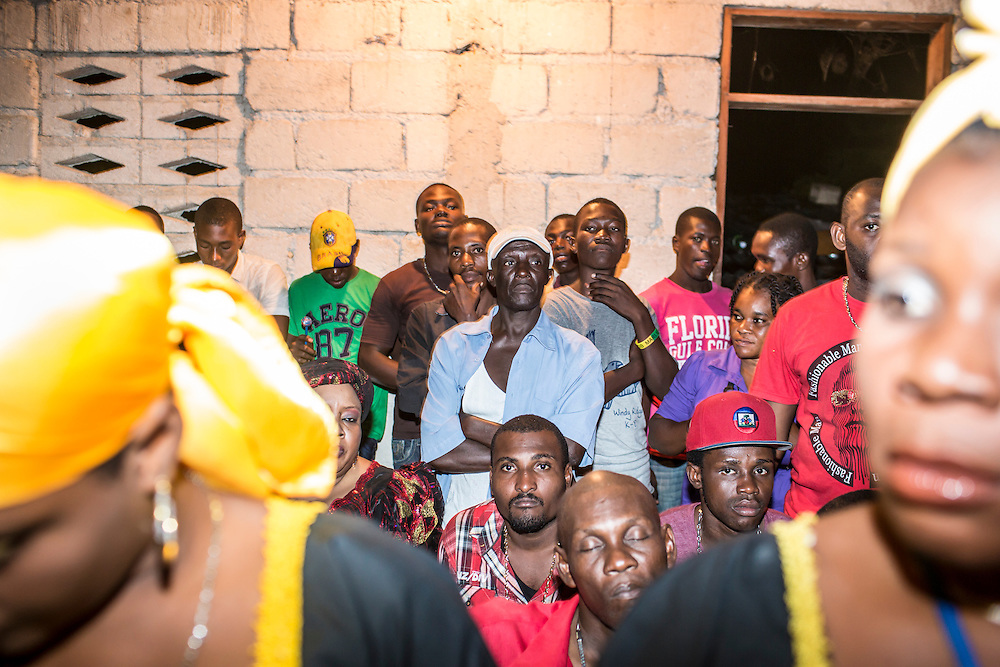Members of the Societe Ti Pilon Baka vodou troupe, foreground, and other worshipers attend a nighttime ceremony on Sunday, December 14, 2014 in Leogane, Haiti. The city of Leogane, about 20 miles west of Port-au-Prince, was the closest city to the epicenter of the 2010 earthquake, and damage there was extensive.